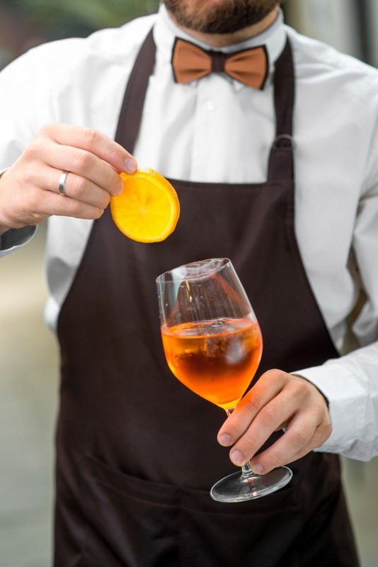Barman making cocktail with sparkling wine, Aperol and orange. Close up view focused on hands